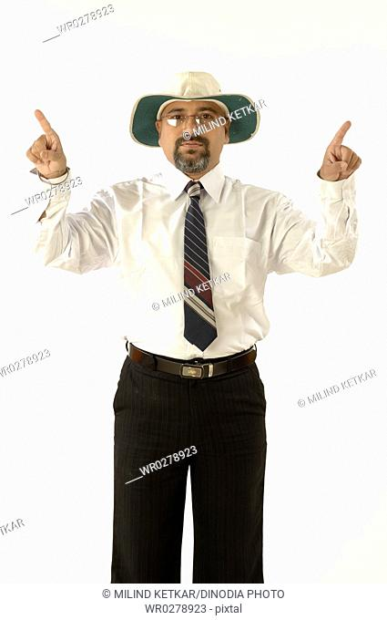 South Asian Indian cricket umpire indicating third umpire sign by raising both hands to mime TV Screen box shape MR705G