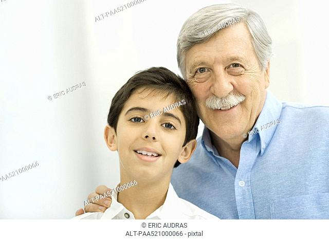 Grandfather and grandson smiling at camera, portrait