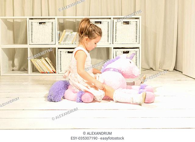 Cute little girl riding on a pink pony toy. Children imagination or creativity concept. Princess and Fairy tale unicorn