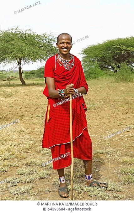 Male Maasai in traditional Shuka clothing with shepherd's crook, Tsavo West National Park, Taita-Taveta County, Kenya