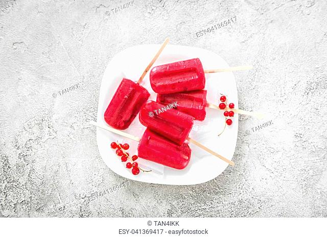 Fresh delicious homemade ice cream popsicles with red currant and berries, topview