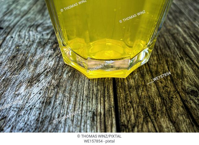 Glass of lemonade on a weathered wooden Table , Germany
