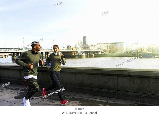 UK, London, man and woman running at riverwalk