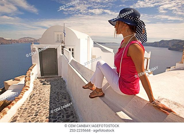 Woman sitting in front of a hotel entrance in Oia town, Santorini, Cyclades Islands, Greek Islands, Greece, Europe
