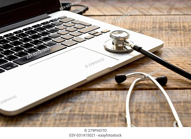 doctor workplace with a stethoscope and laptop at wooden table