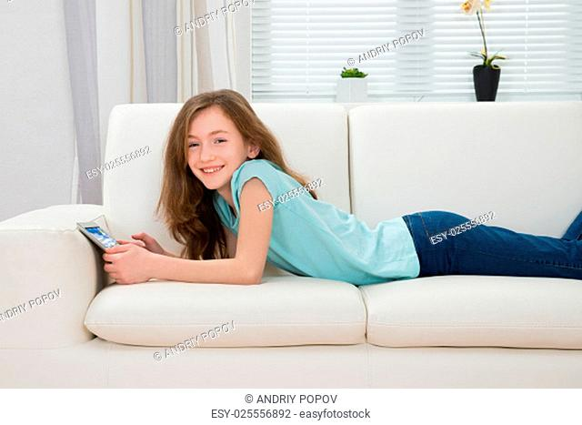 Happy Girl With Digital Tablet Lying On Sofa In Living Room