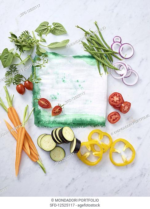 Sliced vegetables on a marble table with a tea towel