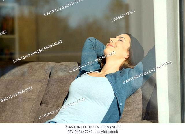 Saisfied tenant girl resting at home on a couch