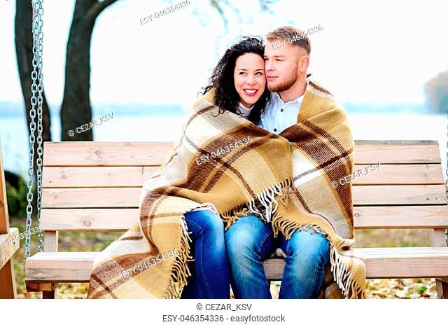 Amorous couple on romantic date on swings outdoor ,autumn