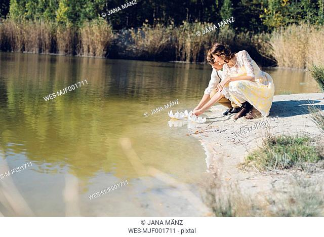 Lovers crouching side by side at water's edge
