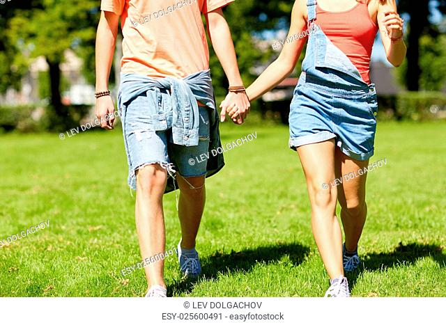 love and people concept - happy teenage couple walking and looking at each other in summer park