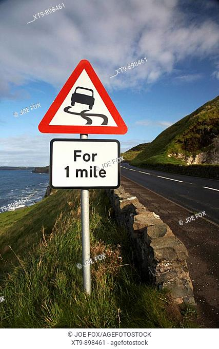 slippery road danger red warning triangle for 1 mile sign on the famous A2 north antrim causeway coastal road route county antrim northern ireland uk