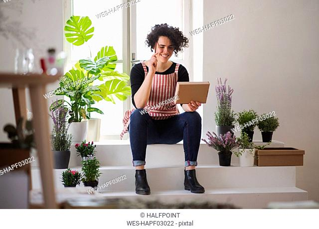 Smiling young woman with cardboard box in a small shop with plants