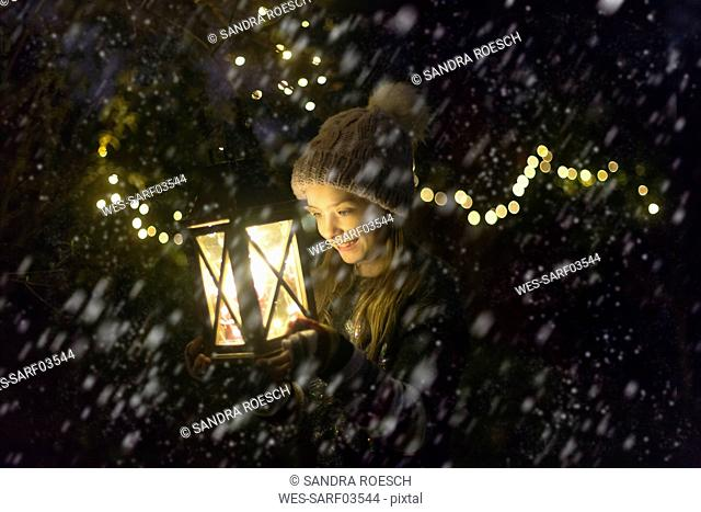 Happy girl with lighted lantern by night at snowfall