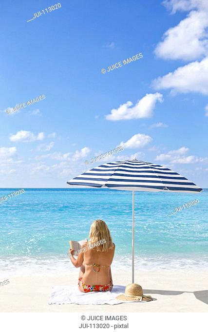 Woman reading book on sunny beach under striped beach umbrella