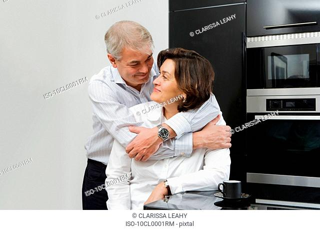 Mature man with arms around wife