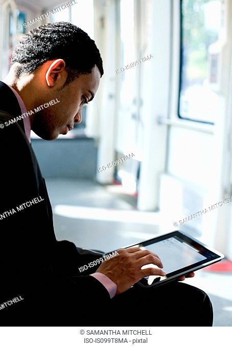 Businessman using digital tablet on a train