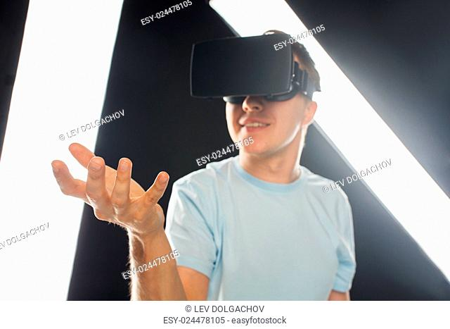 3d technology, virtual reality, entertainment and people concept - close up of happy young man with virtual reality headset or 3d glasses playing game and...