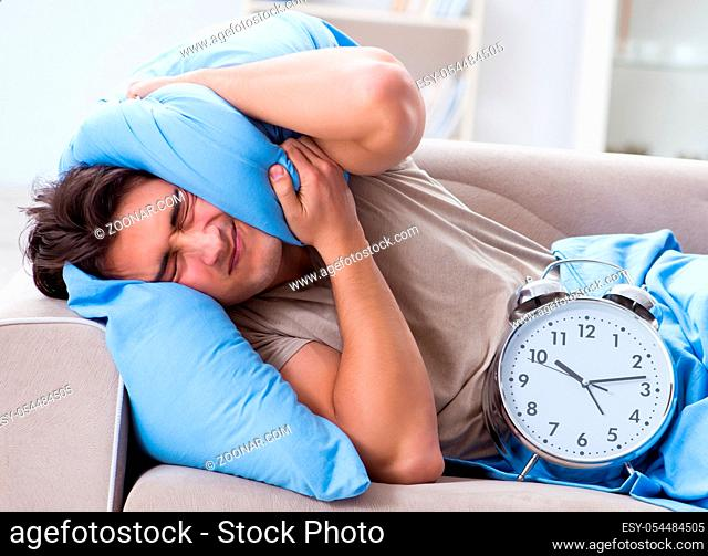 Man having trouble waking up with alarm clock