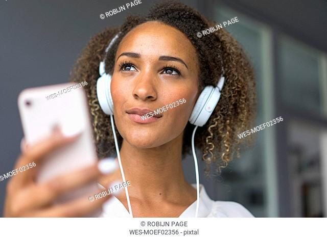 Portrait of young woman with smartphone and white headphones