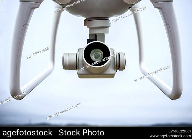 Video camera with gimbal stabilizer placed between both dron legs. Closeup