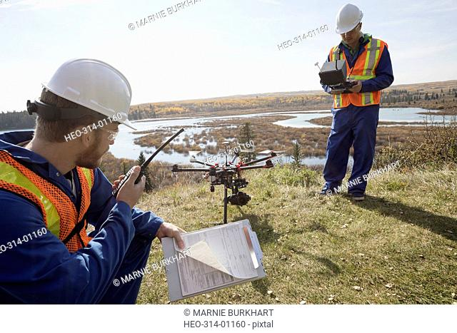 Surveyors with drone equipment and walkie-talkie on sunny hilltop overlooking lake