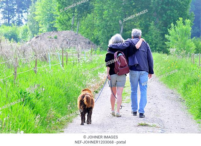 Senior couple with dog walking down footpath