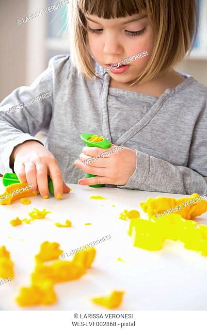 Little girl playing with yellow modeling clay