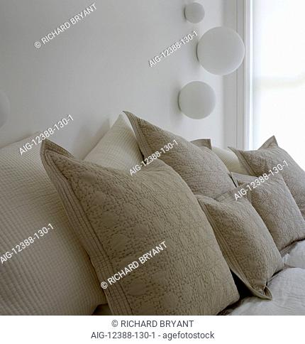 Assortment of cushions on bed in Greencroft Gardens Apartment, London