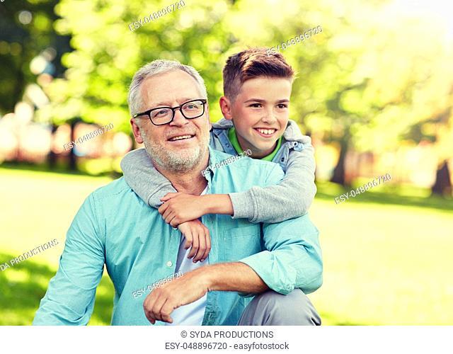 grandfather and grandson hugging at summer park