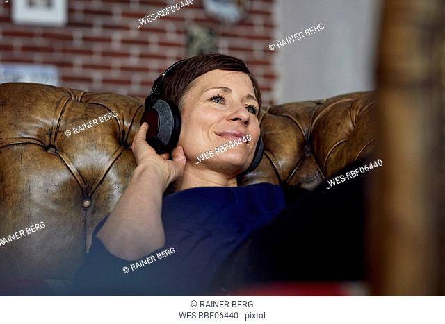 Woman with headphone lying on sofa, listening music