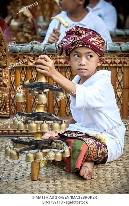 The youngest member of a gamelan orchestra at an event, Ubud, Bali, Indonesia