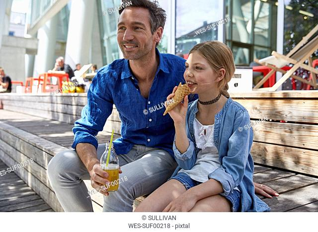 Father with drink and daughter with ice cream cone at an outdoor cafe