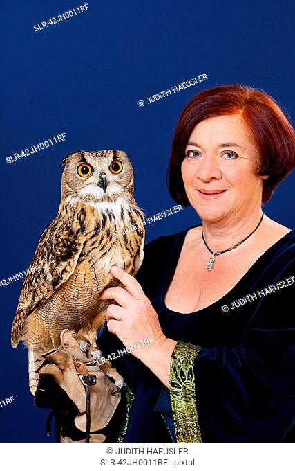 Trainer holding owl on arm