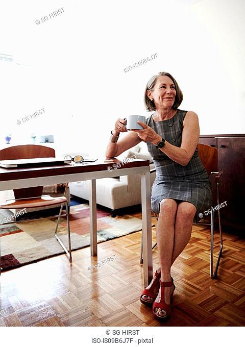 Portrait of senior businesswoman sitting beside desk, holding coffee cup