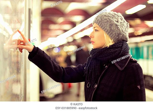 Casually dressed woman wearing winter coat, orientating herself with public transport map panel, pointing on her final destination. Urban transport