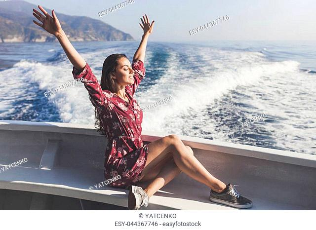 Happy young amazing woman wearing relaxing on the yacht in Cinque Terre, Italy, Ligurian Sea, outdoor
