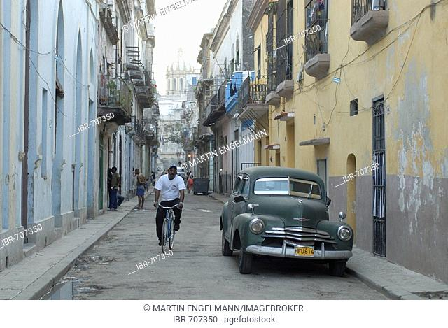 Vintage car and cyclist in an alley in the old part of Havana, Cuba, Caribbean