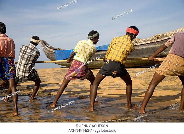 Fishermen pulling nets on shore
