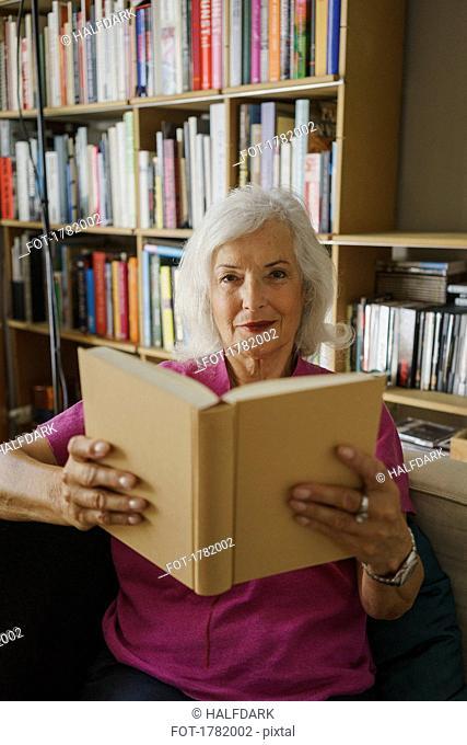 Portrait confident senior woman reading book