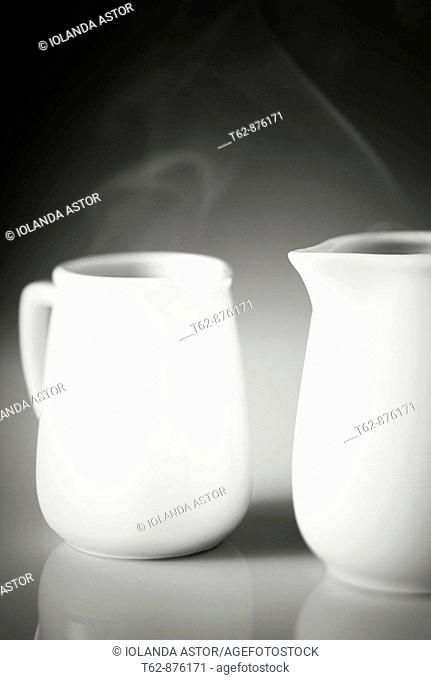 Two white mugs with steaming hot drink