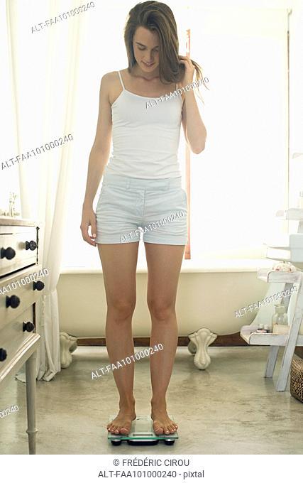Woman weighing self in bathroom