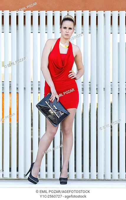 Fanciful young woman in short Red dress facing camera