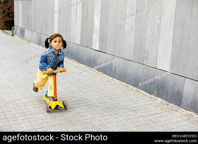 Portrait of little girl riding scooter on pavement