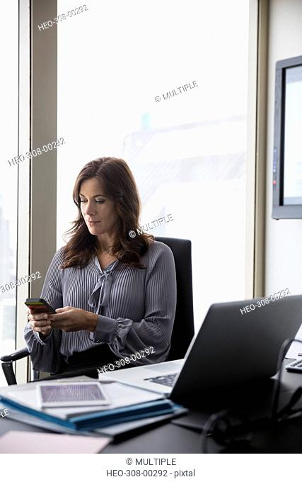 Businesswoman texting at office desk