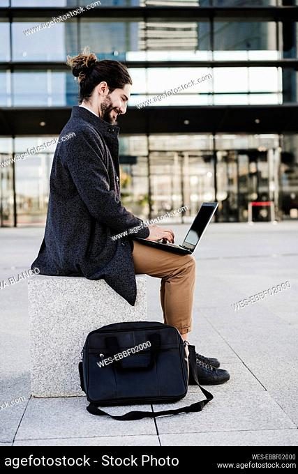 Young entrepreneur using laptop while sitting on bench