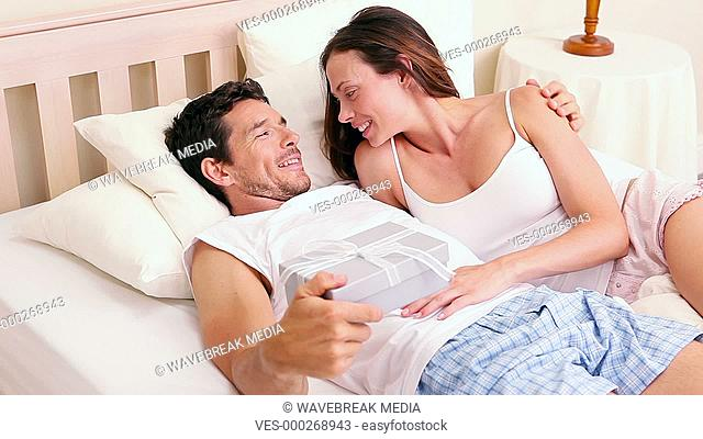 Smiling man giving his girlfriend a gift lying on bed
