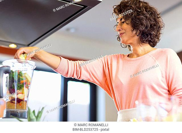 Hispanic woman preparing smoothie in blender