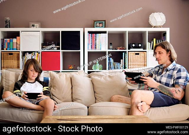 Father and son using technologies while sitting on sofa at home