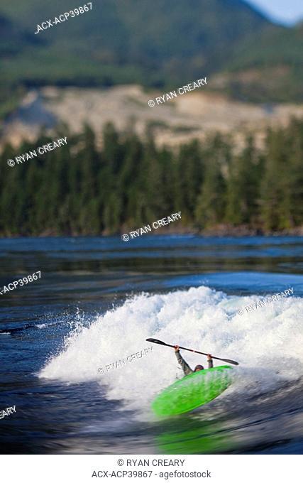 Young man freestyle kayaking on Skookumchuk ocean rapids, Skookumchuck Narrows Provincial Park, Egmont, British Columbia, Canada